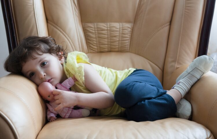 Afraid preschooler curled up in chair shows impact of anxiety in young kids