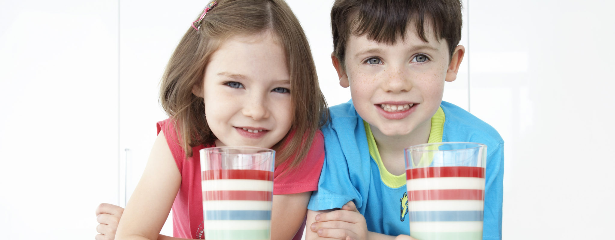 Boy and girl drink milk with lots of vitamin D and calcium