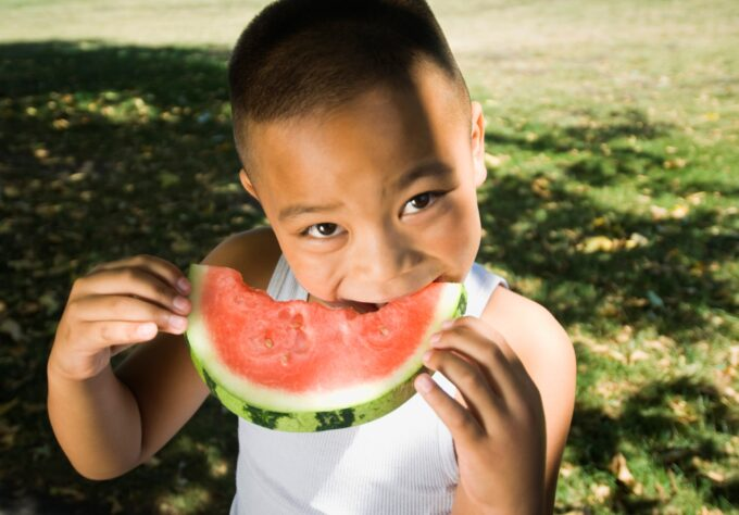 Boy eating seasonal fruits and vegetables.