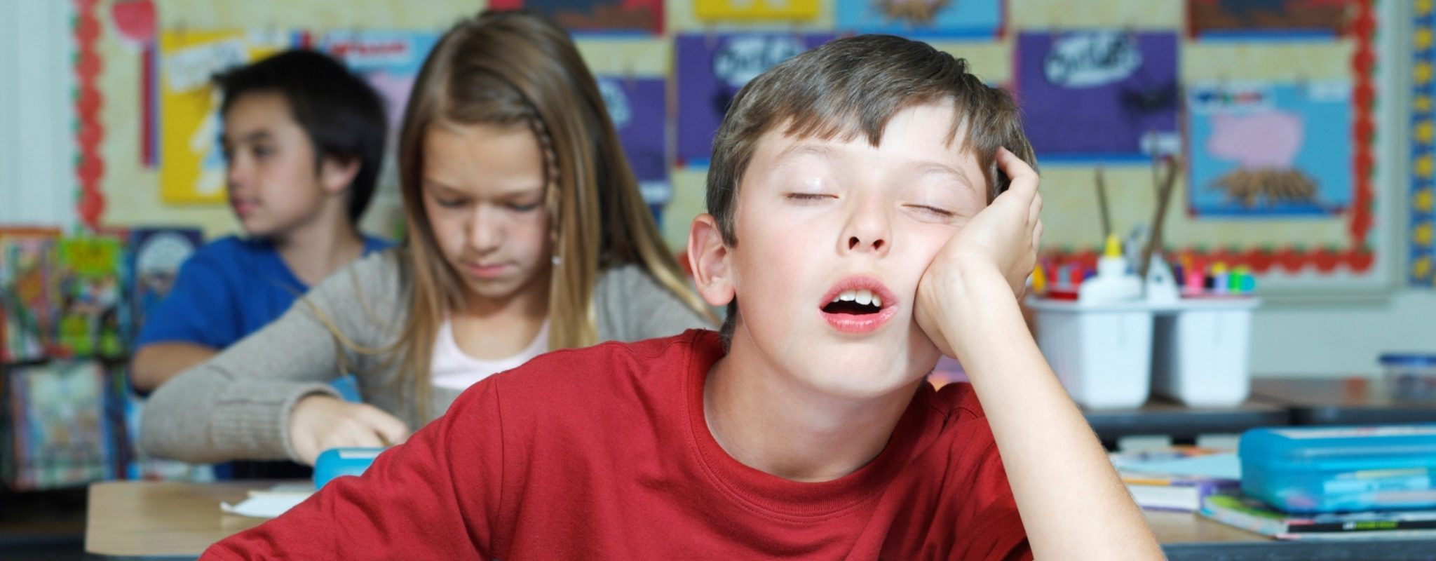Boy sleeping in class needs back-to-school sleep schedule