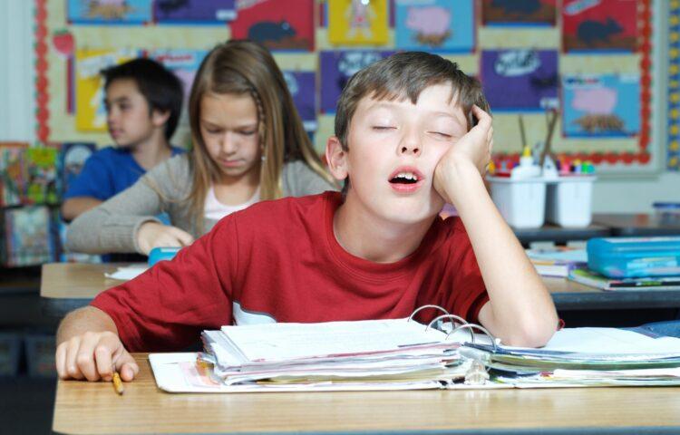 Boy sleeping in class needs back-to-school sleep schedule