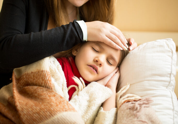 Mom feeling forehead of daughter with fever