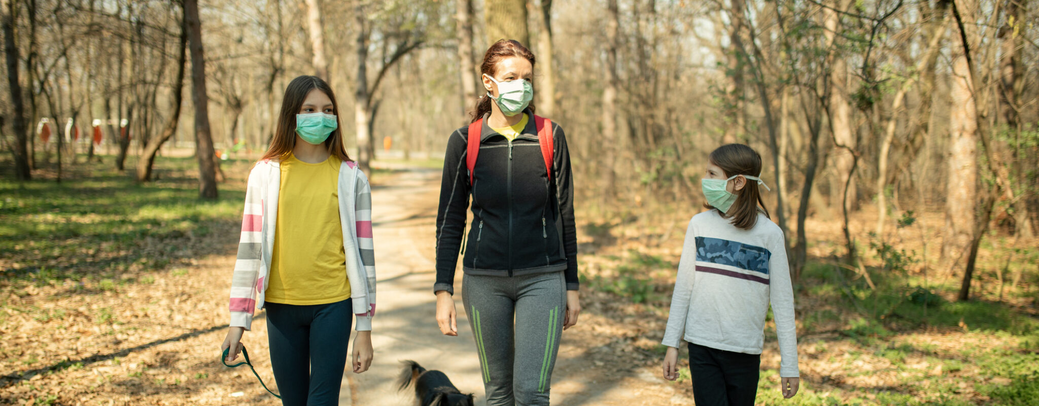 A mother with two children, walking their dog on a trail, wearing masks.