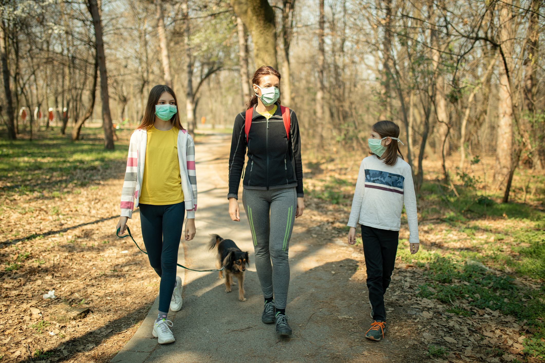 Family walking with their dog in park and wearing mask - Promise