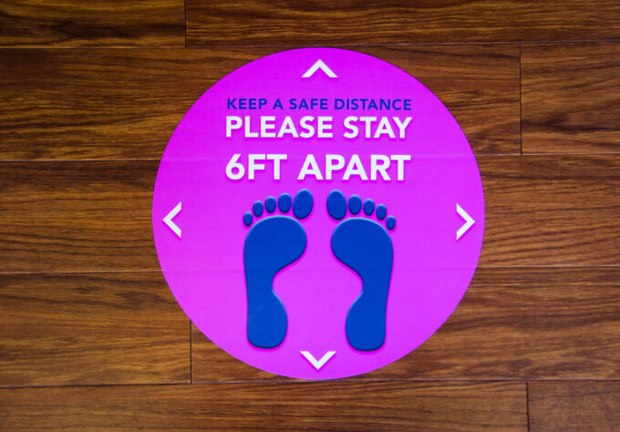 A sticker on the floor reminding people to stay 6 feet apart